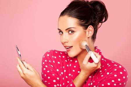 Mooie jonge brunette vrouw blusher op haar wang met een cosmetische kwast en kleine compacte spiegel