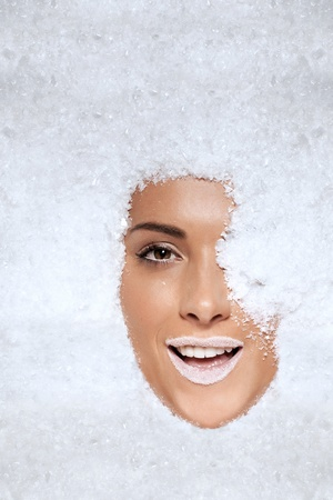 tantalising: Face of a beautiful laughing woman appearing through snow with her one eye still covered and her face completely surrounded with pristine white crystals Stock Photo