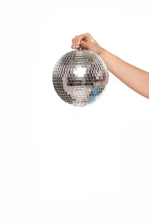 Extended female are holds a small decorative mirrored disco ball over white background, with space for text photo
