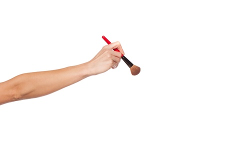 grasp: Cropped studio shot showing an extended female arm and hand holding a make-up brush, isolated over white