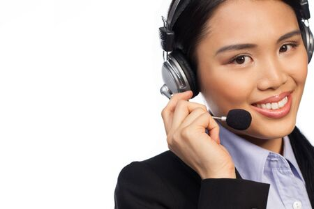 verbal communication: Smiling Asian woman wearing a headset and stylish business jacket, conceptual of a call centre, help desk or receptionist