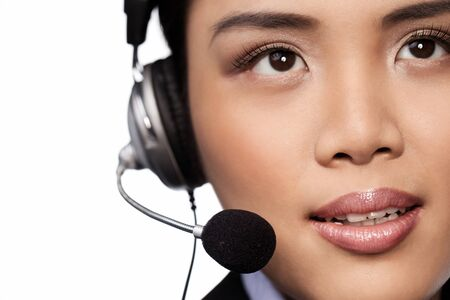 Closeup face portrait of an attractive young Asian lady wearing a headset and microphone conceptual of a call centre operator or receptionist photo