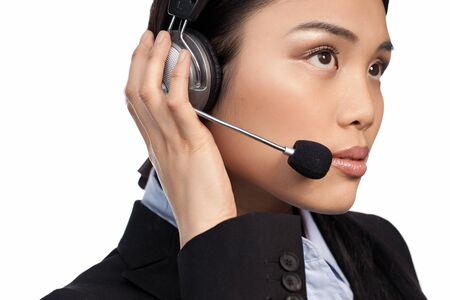 Closeup of a beautiful Asian call centre operator listenng intently to an incomng call isolated on white photo