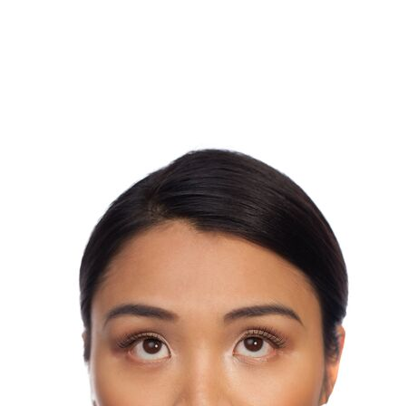 Cropped veiw portrait of the eyes of an Asian woman looking up isolated on white