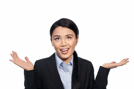 ignorance: Asian businesswoman shrugging her shoulders and raising her palms in the air as she indicates her ignorance or indifference isolated on white