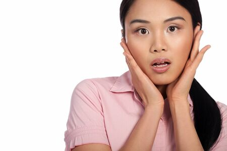 startled: Attracive Asian woman reacting in shock and horror with her eyes wide and hands raised to her cheeks, cropped portrait isolated on white