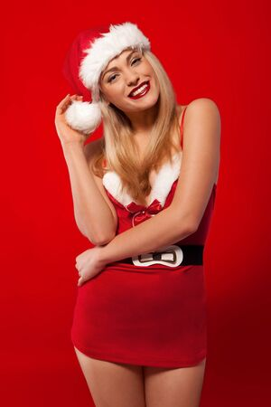 Laughing glamorous blonde woman with a beautiful smile posing in a sexy short Santa costume to celebrate Christmas Stock Photo - 25851339