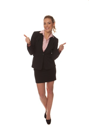 Enthusiastic happy businesswoman in a stylish miniskirt gesturing with her hands as she walks along isolated on white photo