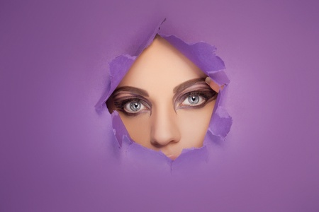 eye hole: Woman with beautiful eyes and creative eye makeup looking through a hole in a sheet of purple paper so that only her eyes are visible