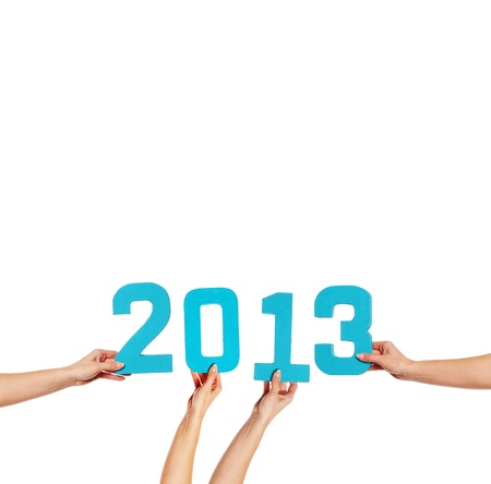 2013 greeting card with blue numerals held up by female hands isolated against a white background with copyspace for your New Year greeting photo