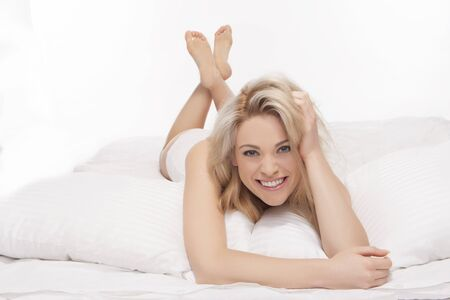 vivacious: Fresh studio portrait of a gorgeous vivacious blonde woman lying on her bed in lingerie facing the camera laughing with plenty of copyspace overhead