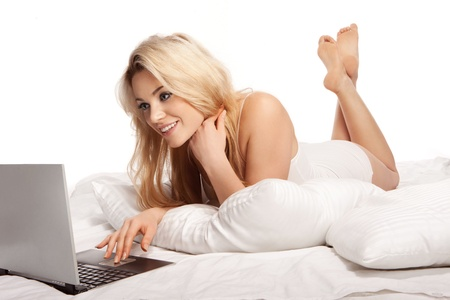 stunning: Charming blonde woman with a lovely smile lying on her bed on her stomach using a laptop