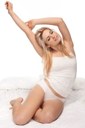 rejuvenated: Gorgeous young blonde woman sitting on her bed in sleepwear stretching as she wakes up Stock Photo