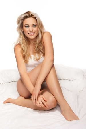 Sexy graceful young blonde girl sitting on her bed in lingerie with her shapely bare legs pulled up in front of her smiling happily at the camera photo