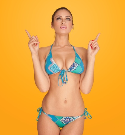 Looking up woman wearing two piece bikini pointing up her hands Stock Photo