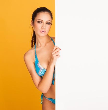 brunette bikini girl holding a white blank board for a text photo