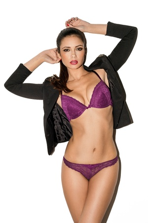 Sexy brunette fashion model with a lovely shapely figure posing in purple lingerie and a trendy jacket with her arms raised , isolated on white Stock Photo
