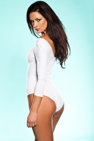 facing away: Provocative woman in a white leotard looking back over her shoulder at the camera with a sultry look on a blue studio background