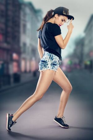 runs: Sexy young woman hip hop dancer in shorts and a cap performing in the centre of a street