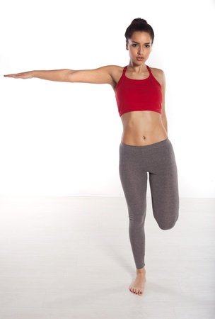 arm extended: Woman doing balancing exercises standing on one foot with her arm extended outwards to the side isolated studio portrait