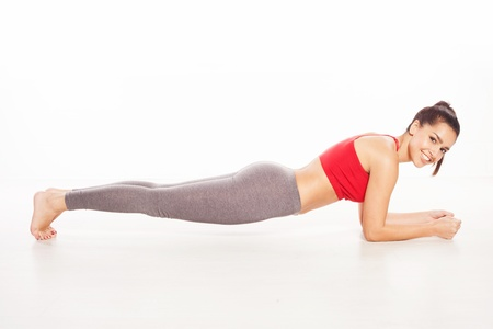 push up: Barefoot smiling young woman practicing push-up exercises on the floor Stock Photo