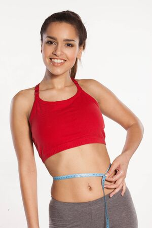 Woman measuring her waist with a smile satisfied with the results of her exercise regime isolated on white Stock Photo