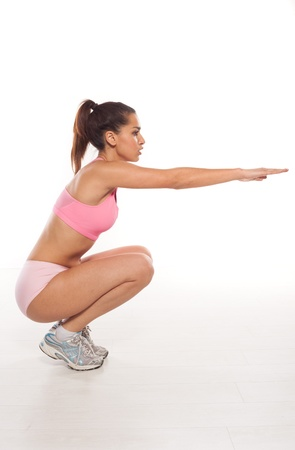crouched: Woman working out doing aerobics crouched down on her haunches with her arms extended straight out in front of her Stock Photo