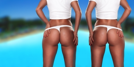 Twin sexy asses, two women, toned behinds in white thong facing away from the camera, shoulders down shot photo