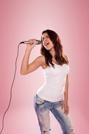 kareoke: sexy singer holding a microphone wearing white top and jeans Stock Photo