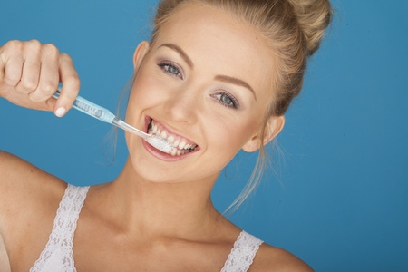 Sexy woman on blue brushing her teeth  Stock Photo