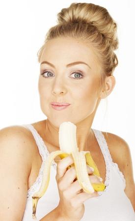 comiendo platano: Mujer atractiva en blanco que come el plátano Foto de archivo