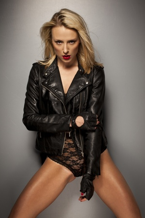 Seductive woman posing in a black leather jacket, gloves and lacy lingerie giving the camera a sultry look photo