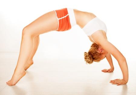 arching: Ajuste a la mujer en ropa deportiva el�stica arqueada sobre su espalda para que sus dedos de los pies y las pallams de sus manos toquen el suelo en un concepto de fitness amd salud sobre un fondo blanco Foto de archivo