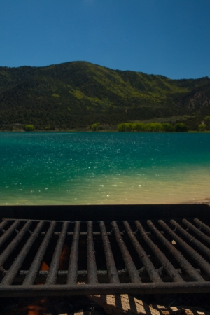 Empty metal bars of a barbecue grid above a scenic mountain lake Stock Photo - 21338443