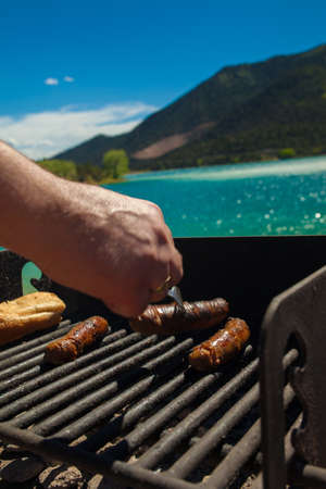 Hand of a man cooking sausages over a barbecue with a beautiful mountain lake on the background photo