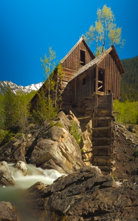 View of Crystal Mill and the Crystal River with the historical wooden power house that use to drive an air compreesor for the silver mines via a waterwheel perched on a rocky outcrop above the river