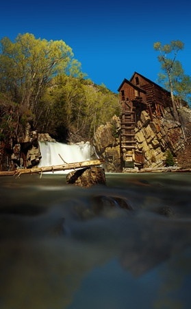 mining town: Old wooden building standing on top of a cliff close to a river waterfall in Crystal Mill Ghost town, Colorado, USA