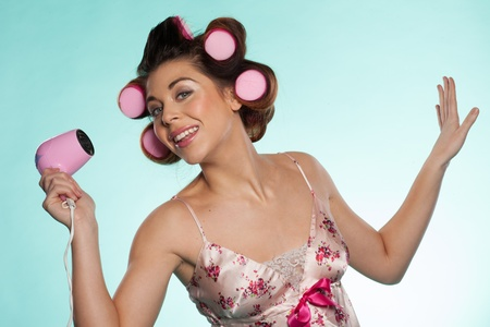 haircurlers: Fun portrait of an attractive woman in outsized pink haircurlers with a hairdryer in her hand posing for the camera against a blue background