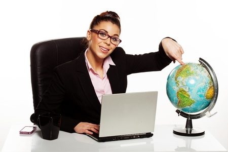 Smiling manageress or businesswoman wearing glasses sitting at her desk pointing to North America on a world globe photo
