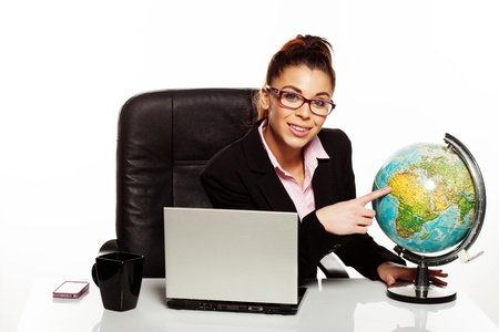 Businesswoman wearing glasses with a world globe on her desk pointing with her finger to West Africa photo