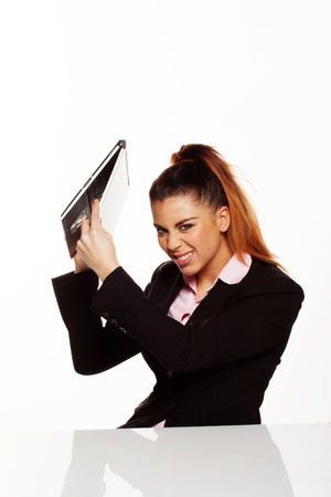Angry businesswoman about to smash her laptop on the desk isolated on a white background photo