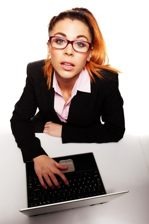 Fun overhead portrait of a young businesswoman sitting at her laptop computer wearing glasses and looking up expectantly at the camera photo