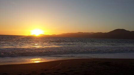 laps: Vivid orange sun setting over the ocean as it drops below the mountains while gentle surf laps on a sandy deserted beach in the foreground