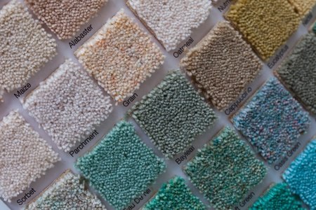 Colourful carpet display in a shop with square samples wall mounted in a variety of colours to plan your interior decor and renovation Foto de archivo