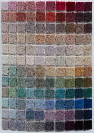 Display of multiple small square carpet samples in an interior decor store covering all the colours of the spectrum Stock Photo - 21338489