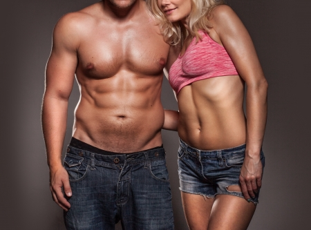 Fitness image of a man and womans torso isolated on black