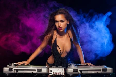 Glamorous DJ tetona sexy en el trabajo de mezcla de sonido en sus cubiertas en una fiesta o discoteca con colores de fondo humo luz Foto de archivo - 25853006