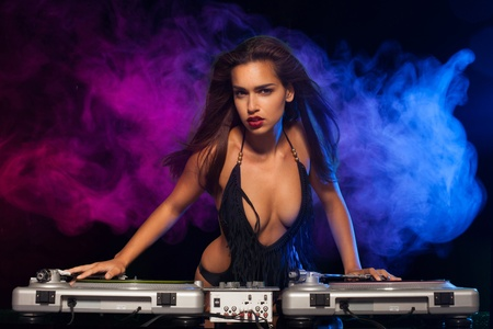 Glamorous sexy busty DJ at work mixing sound on her decks at a party or night club with colourful smoke light background