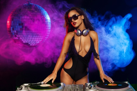Glamorous sexy busty DJ at work mixing sound on her decks at a party or night club with colourful smoke light background photo