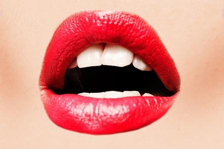 Mujer joven hermosa con los labios rojos atractivos entreabiertos en anticipación sensual, opinión